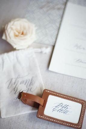Brown leather luggage tag with a white thank you pouch, white rose and a card