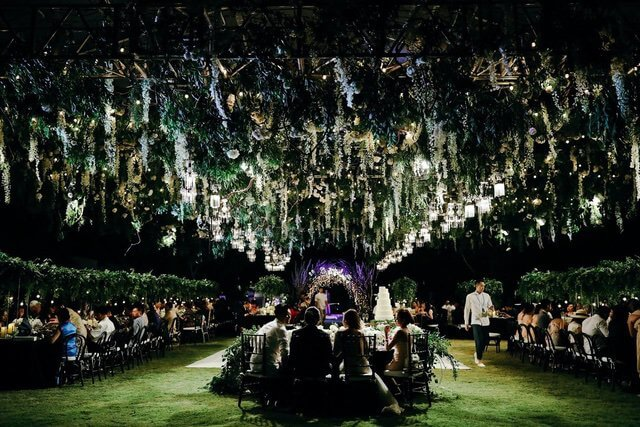 Dramatic hanging green flowers and lanterns over dining guests