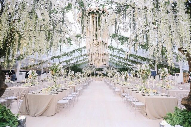 Transparent marquee with lots of hanging white flowers aboe very long tables