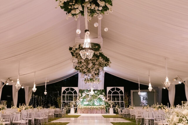 Dramatic hanging chandeliers above wedding reception