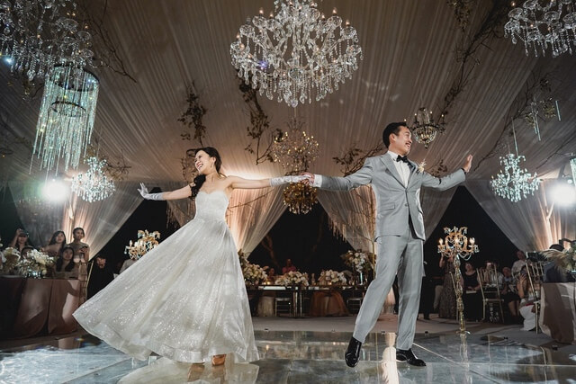 Bride and Groom dancing on mirror dance floor under crystal chandeliers