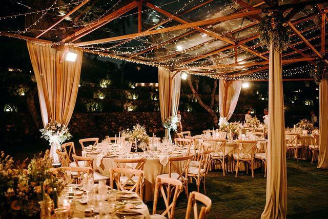 Round tables and wooden chairs inside wooden marquee at night