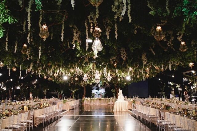 Lots of hanging lanterns and green foliage above dining area with wedding cake