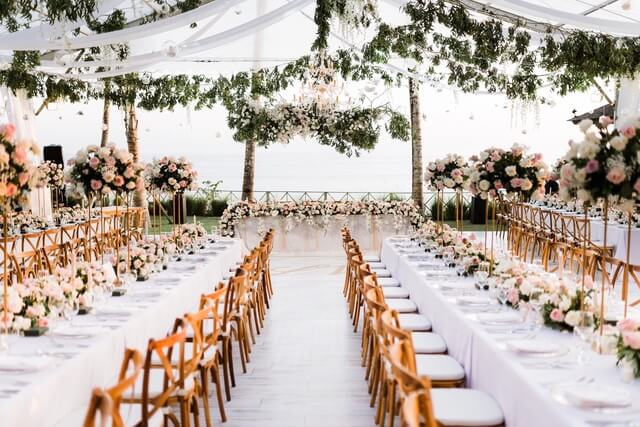 Open air marquee above long white linen tables with wooden chairs