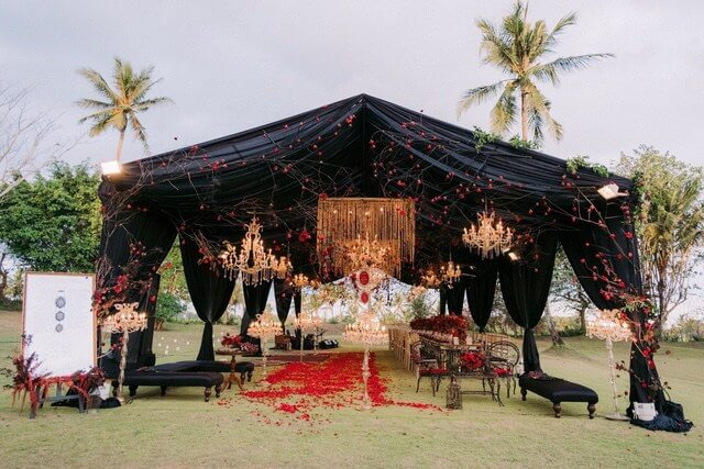 Black marquee in garden with hanging illuminated crystal chandeliers and red roses on the grass