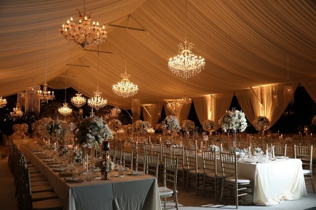 Inside long marquee with hanging illuminated chandeliers and long tables with flower centerpieces