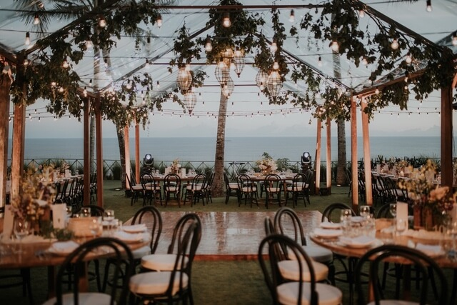 Wooden dance floor surrounded by tables and chairs overlooking ocean