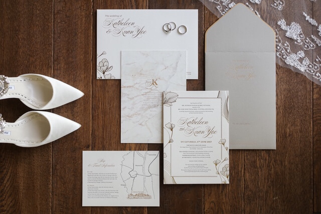 Wedding invitation and literature with silver rings and white shoes on wooden floor