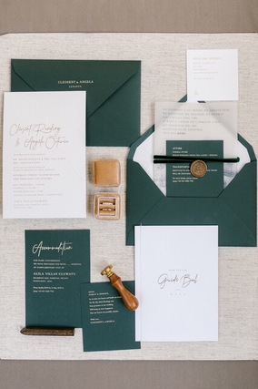 Wedding invitation and literature on white paper and green paper with green envelope