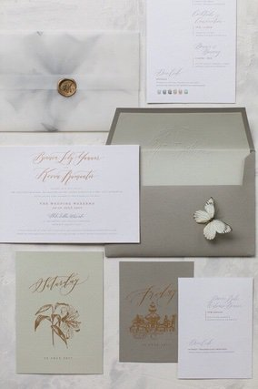 Wedding invitation on white paper with grey envelopes and little model of butterfly