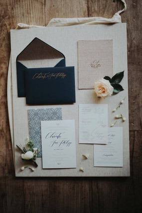 White card wedding invitation with dark blue envelope and peach coloured flower on a wooden floor