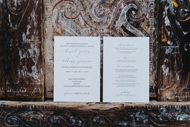 Letterpress wedding invitation displayed against dark wooden panel