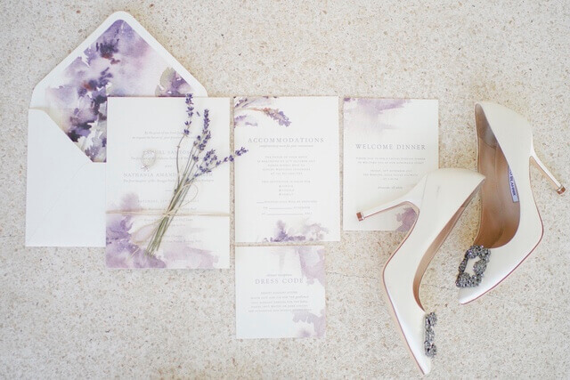 Wedding invitation and envelope with creme and purple design next to Bride's high heeled shoes
