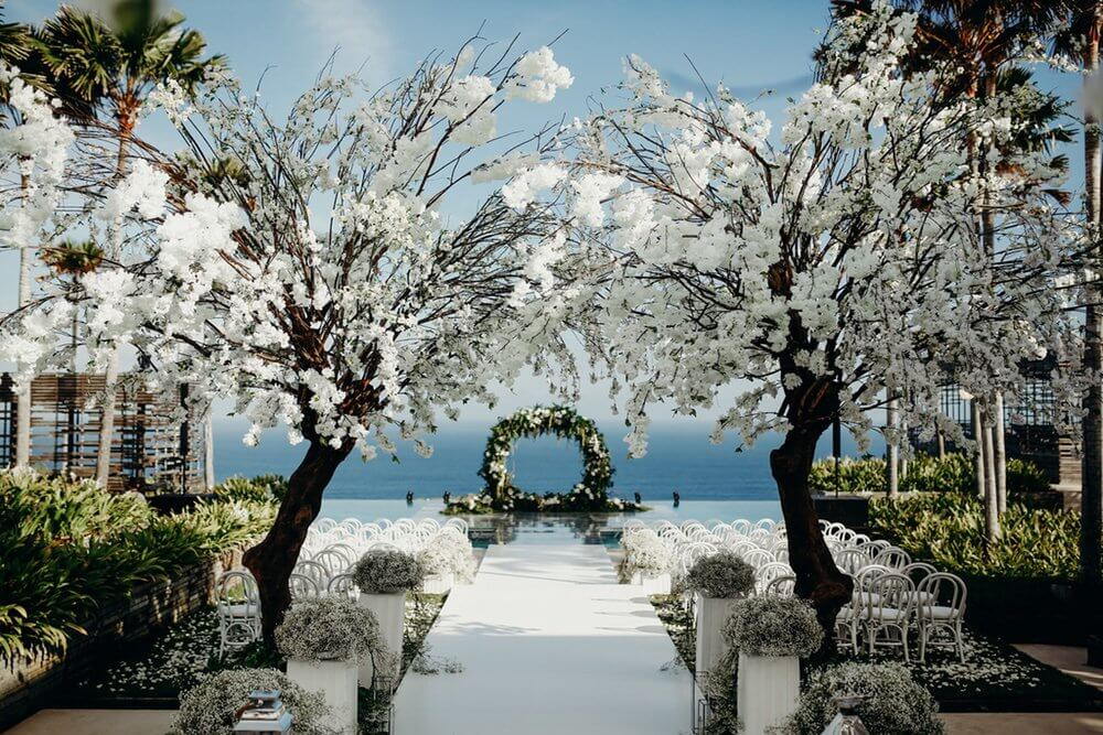 Two white leaved trees and white wedding chairs either side of aisle
