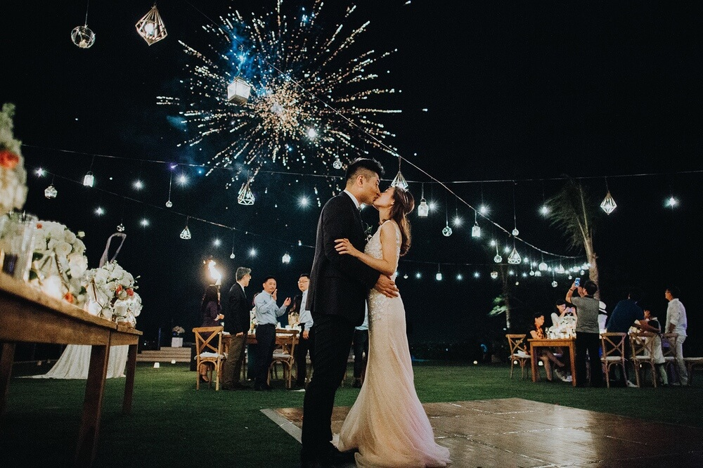 Newlyweds kissing on dancefloor under exploding fireworks
