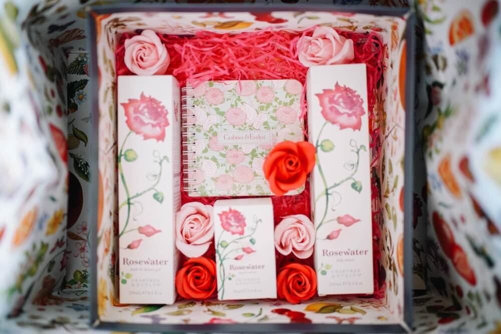 Box containing wedding gifts and pink and red roses