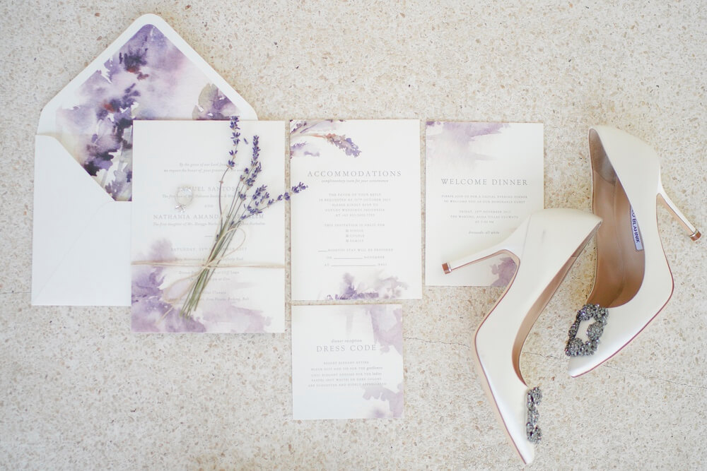 Purple and white wedding invitation and envelope with brides high heeled shoes