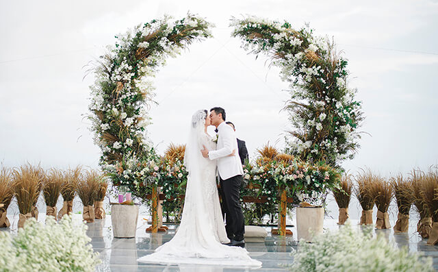Bride and Groom kissing at the altar with green flower arch
