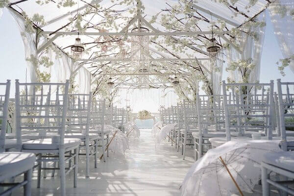 White flower canopy above white wedding chairs and white umbrellas
