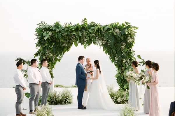 Bride and Groom holding hands during wedding ceremony below green flower arch