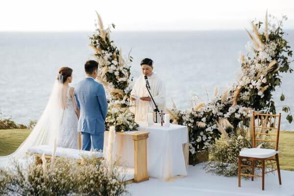 Pastor conducting prayer with Bride and Groom in front of large wedding arch