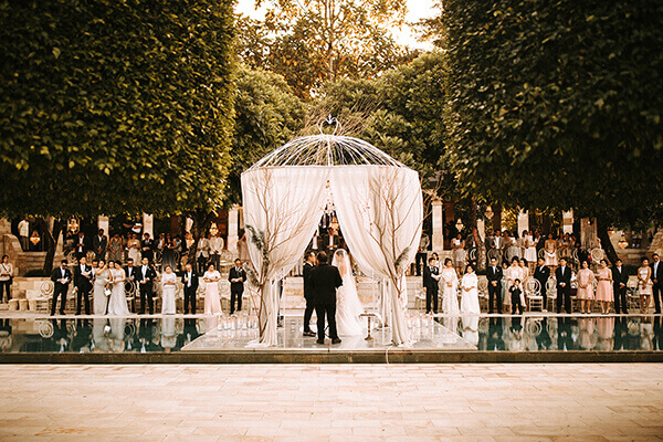 Bride and Groom inside a white pergola on a floating stage above a swimming pool