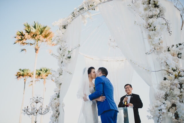 Bride and groom kissing under a white iron pergola adorned with white lace and white roses