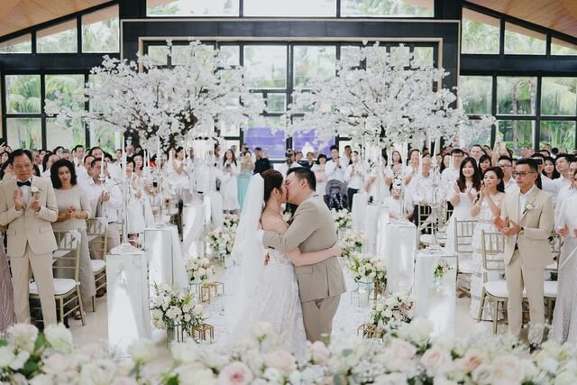 Bride and groom kissing with guestsclapping in Mulia Resort Bali's Eternity chapel