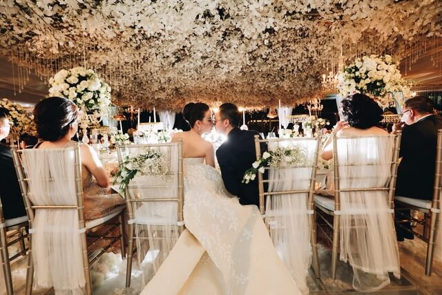 Bride and groom kissing whilst seated at the bridal table