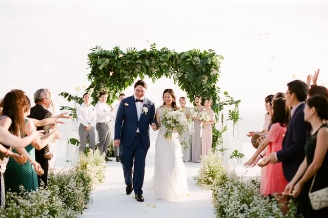 Bride and Groom walking together down aisle