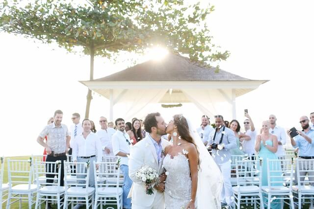 Brdie and groom kissing in front of wedding guests in front of a white bale