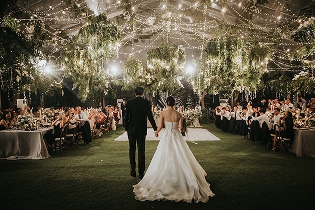 Bride and Groom standing before wedding guests in a large marquee with hanging lights