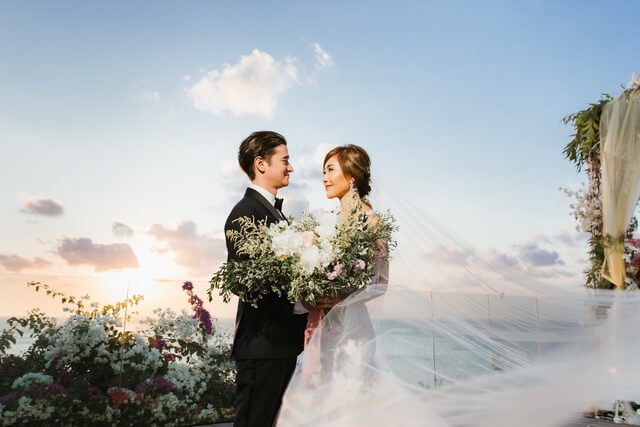 Bride holing large floral bouquet with Groom during sunset