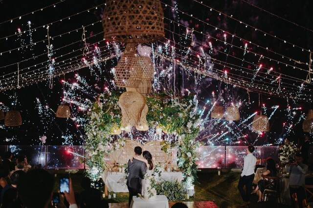 Bride and Groom hugging at the bridal table watching an intense firework display