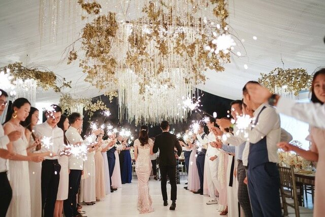 Bride and Groom walking oast guests with sparklers