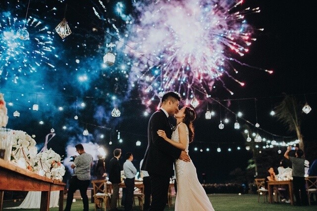 Bride and groom kissing with firworks exploding above