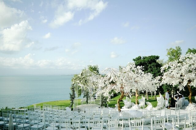 Outdoor wedding ceremony on grass amphitheatre overlooking the ocean