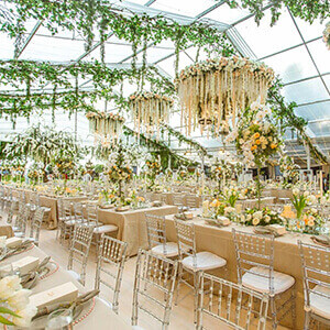 A giant transparent PVC wedding marquee with flower chandeliers and wooden flooring.