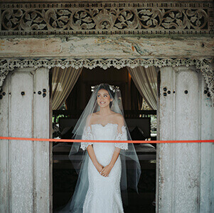 Bride waiting in a doorway blocked by a long length of red ribbon