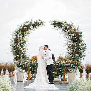 Bride and Groom kissing at the wedding altar in front of elaborate curved flower arch