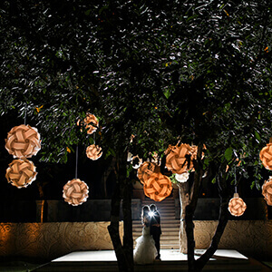 Couple dancing in the dark underneath orange lanterns hanging from a tree