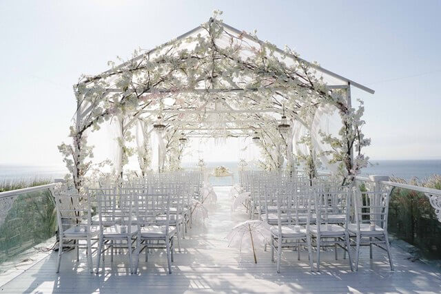 Bali wedding ceremony decor of white chairs under a tent like frame covered in white and pink flowers