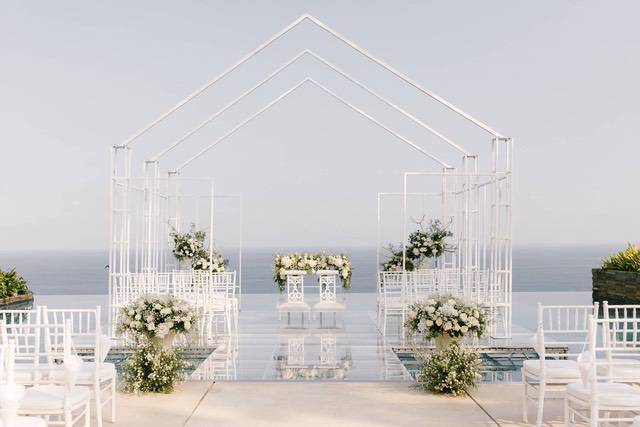 Wedding ceremony setup with metal house shaped frome with white chairs and flowers underneath