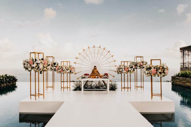 Floating wedding ceremony stage with Buddha statue surrounded by standing flowers