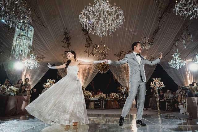 Bride and Groom dancing under crystal chandelier in wedding marquee