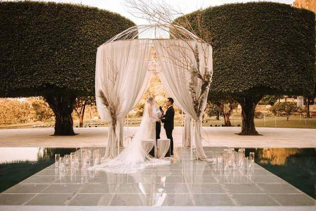 Bride and Groom taking vows under white pergola with white drapes on floating stage