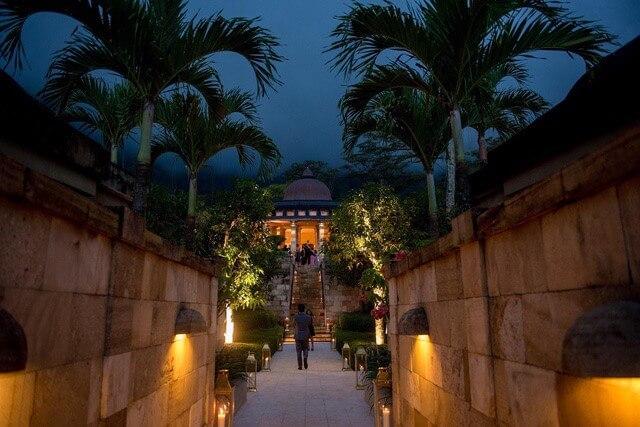 Guests walking towards staircase in Amanjiwo Resort at night