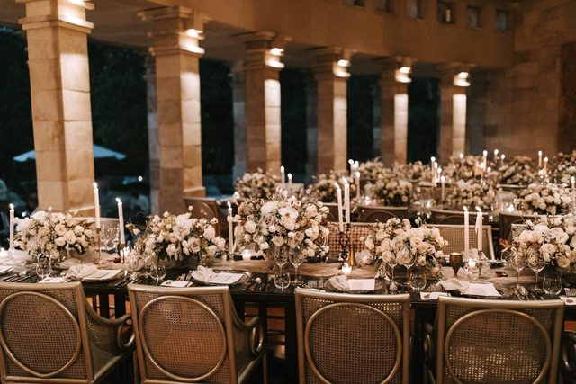 Table decorated with floral centerpieces and candle sticks with gold chairs