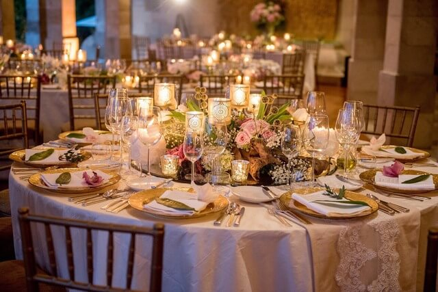 Round table set for dinner with flower and candle adornments