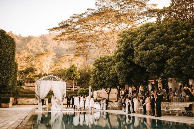 Floating stage with wedding guests standing around swimming pool in Amanjiwo Resort